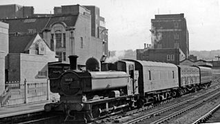 A pannier tank locomotive pulling a train of three wagons through a station. The coaches are a parcel van, a goods wagon, and a passenger coach.