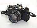 Olympus OM-4Ti worn black body with Zuiko 1.8-50mm lens and neckstrap.jpg