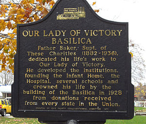 Our Lady of Victory Basilica (Lackawanna, New York) - A sign describing the basilica's important status amongst Father Nelson Baker's several charitable institutions of Our Lady of Victory parish.