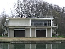 A two-storey building on a river bank. There are railings at balcony and roof level, two flag poles (one on the far left of the roof, one on the far right), external spiral staircases leading to roof level (one on the far left of the building, the other on the far right) and two large doors at ground level at the front.