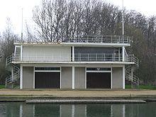 Двухэтажное здание на берегу реки.  На балконе и на уровне крыши есть перила, два флагштока (один в дальнем левом углу крыши, один в крайнем правом углу), внешние винтовые лестницы, ведущие на уровень крыши (одна в дальнем левом углу здания, другая - на крайний справа) и две большие двери на уровне земли спереди.