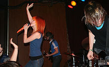 A band performs for a live audience. Two men are playing guitars while a woman with bright red hair sings into a microphone.