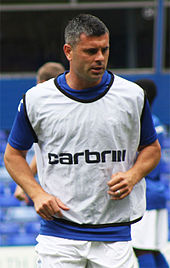 Grey-haired man wearing blue and white sports clothing