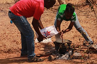 Pap (food) - A man and a Woman cooking Pap in Botswana (Domboshaba Cultural festival 2017)