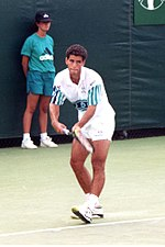 A black-haired man in white shorts and a white shirt prepares to serve with a modern racket