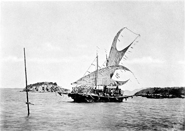 Black and white photograph of a moored sailing boat, with an island visible a short distance behind it.