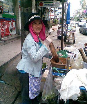 Green papaya salad - Street vendor from Isan pounding green papaya salad in Bangkok