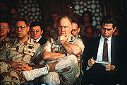 Powell (left) sits alongside Paul Wolfowitz (right) and Norman Schwarzkopf  (middle) listening as Secretary of Defense Dick Cheney hosts a press conference regarding the War.