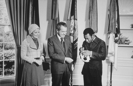 "Pele signing a football for U.S. President Richard Nixon at the White House in 1973, two years before joining the New York Cosmos President Nixon meeting with Edson ""Pele"" Arantes do Nacimento, retired professional Brazilian soccer player and... - NARA - 194508.tif"