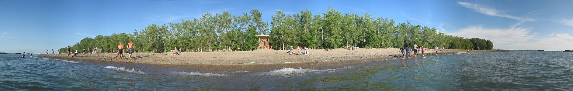 A view of a sunlit beach, that is flanked by green trees, from the water under a mostly clear, blue sky with several vacationers.