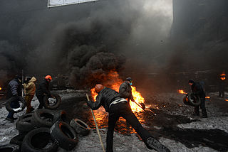 Protesters throwing tires to the fire set by the protesters to prevent internal forces from crossing the barricade line. Kyiv, Ukraine. Jan 22, 2014.jpg