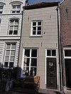 foto van Eenvoudig huis met gebosseerd geelgepleisterde lijstgevel, schilddak, ankers