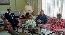 Une femme et deux hommes parlent ensemble, assis dans des canapés