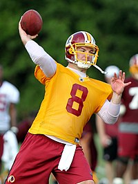 Rex Grossman, in yellow non-contact practice jersey, throws a football in a Washington Redskins practice.