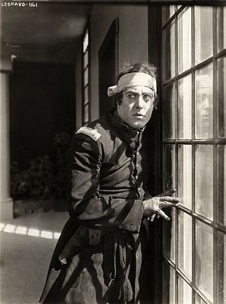 "Robert Z. Leonard - Robert Z. Leonard, costumed as a U.S. Army first lieutenant during the Civil War, pauses by a window in a scene still for the 1915 silent drama ""Betty's Dream Hero."""