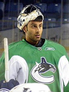 "An ice hockey goaltender with his mask pulled off of his face looking forwards. He wears a green jersey with a logo of a stylized orca in the shape of a ""C""."