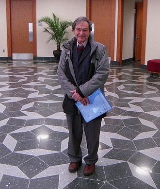 Penrose tiling - Roger Penrose in the foyer of the Mitchell Institute for Fundamental Physics and Astronomy, Texas A&M University, standing on a floor with a Penrose tiling