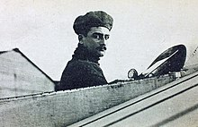 Bust and head of Roland Garros emerging from open cockpit of aircraft, looking at viewer