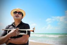 Roy Paci con la sua tromba e l'orizzonte del mare. Scatto di Barbara Ledda.