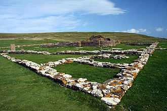 Brough of Birsay - The remains of houses with the church and, on the left, the replica Pictish stone