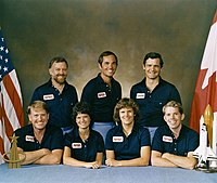 frente, e-d: JonMcBride, Sally Ride, Kathryn Sullivan e David Leestma. Em pé, e-d: Scully-Power,  Robert Crippen e Marc Garneau.