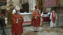 Двое мужчин в масках, митрах и красных облачениях стоят перед алтарем.  Служители алтаря, дьяконы и священники на заднем плане также носят маски.