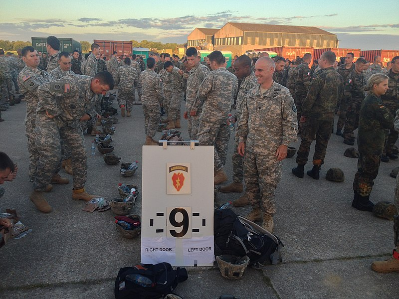 Lt. Col. Clint Baker (right), commanding officer of 1st Squadron (Airborne), 40th Cavalry Regiment and the former commander of 1st Battalion (Airborne), 501st Infantry Regiment, stands with other members of the 4th Infantry Brigade Combat Team (Airborne), 25th Infantry Division as they prepare to draw parachutes June 8 at the airport in Cherbourg, France. The trip to Normandy gave Baker the opportunity to walk the ground where his former unit fought during World War II.