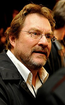 A lightly bearded and bespectacled brown-haired middle-aged Caucasian man wearing a jacket and white shirt with an open collar looks to the camera's right