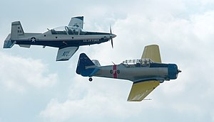 North American T-6 Texan - An original T-6 Texan aircraft (painted as a US Navy SNJ), right, with the new T-6 Texan II, left, at Randolph Air Force Base, Texas, in 2007
