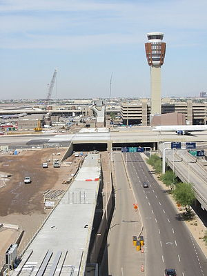 PHX Sky Train - Phase 1a construction as of May 2013, viewed from Terminal 4 to T3. The concrete guideway, largely complete, dives under Taxiways S and T, then rises to enter the skeleton of the T3 station