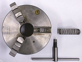 Chuck (engineering) - Self-centering three-jaw chuck and key with one jaw removed and inverted showing the teeth that engage in the scroll plate. The scroll plate is rotated within the chuck body by the key, the scroll engages the teeth on the underside of the jaws which moves the three jaws in unison, to tighten or release the workpiece.