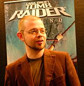 A short-haired man with a beard standing in front of an advertisement poster. The man wears glasses and a light brown jacket over a brown top.