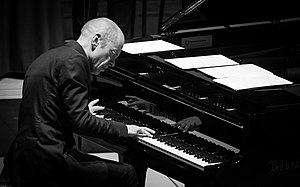 A black-and-white photo of a man playing a piano; he is hunched over it and is concentrating deeply.