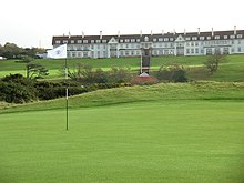 A wide, sprawling golf course. In the background is the Turnberry Hotel, a two-story hotel with white facade and a red roof. This picture was taken in Ayrshire, Scotland.