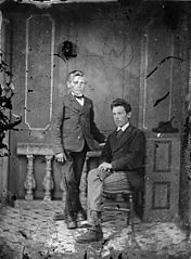 Two young men, one standing and the other sitting