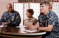 U.S. Navy Religious Program Specialist 1st Class Cecilia Marrero, center, selected for promotion to chief petty officer, sits between Capt. Steven Wieman, right, commanding officer of Naval Air Facility (NAF) 130813-N-OX321-031.jpg