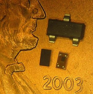 Chip-scale package - Example WL-CSP devices sitting on the face of a U.S. penny. A SOT-23 device is shown for comparison.