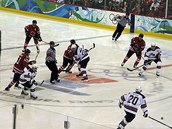 "An ice hockey game. Two referees in black and white striped shirts are visible, as are four players from each team. One team is wearing red jerseys with a maple leaf on the front, and the other is wearing white jerseys with blue accents and the letters ""U-S-A"" on the front."