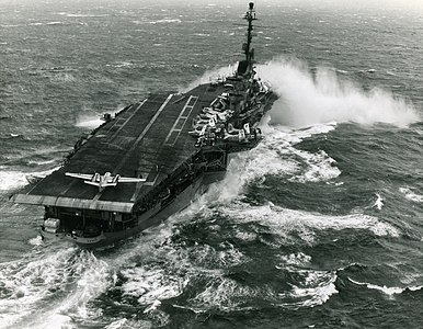 "In this historical photograph, ""USS Essex (CVA-9) takes spray over the bow while steaming in heavy seas. Essex, with assigned Carrier Air Group 10 (CVG-10), was deployed to the Mediterranean Sea from 7 August 1959 to 26 February 1960."""