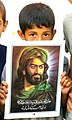 US Navy 030614-M-4066S-012 An Iraqi boy holds up a picture of a religious icon in the Muslim city of Al-Kut.jpg