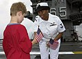 US Navy 040429-N-6268K-012 Intelligence Specialist 2nd Class Tashawbaba McHerrin hands an American flag to a child on the ship's flight deck.jpg