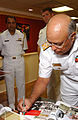 US Navy 040727-N-8148A-006 Chief of Naval Staff, Pakistan Navy, Adm. Shahid Karimullah, signs his name on the guest book of Capt. James Symonds.jpg
