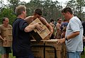 US Navy 050901-N-8047K-121 U.S. Navy Sailors and civilian personnel unload food and water from a UH-3H Sea King helicopter, transported from Naval Air Station Pensacola, Fla., to provide support and relief to victims of Hurrica.jpg