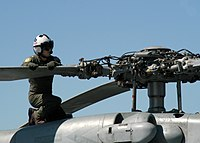 US Navy 050908-N-6495K-058 U.S. Navy Lt. Cmdr. Rex Kenyon checks the rotor head of an SH-60F Seahawk.jpg