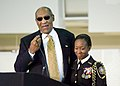 US Navy 061003-N-0000K-001 Dr. William H. Bill Cosby congratulates Keisha Dewberry, a senior Navy JROTC battalion commander at Frederick Douglass High School, on her accomplishment.jpg