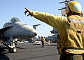 US Navy 071031-N-1287L-112 An aviation boatswain's mate directs an F-A-18C Hornet, attached to the Sidewinders of Strike Fighter Squadron (VFA) 86, onto one of the four steam-powered catapults.jpg