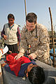 US Navy 071128-M-7696M-156 Lt. Cmdr. Trey Hollis, chief surgeon of the 22nd Marine Expeditionary Unit (MEU) (Special Operations Capable) Command Element, renders medical aid to a victim of Tropical Cyclone Sidr in South Khali.jpg