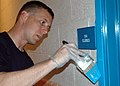 US Navy 080819-N-9793B-014 Air Traffic Controller 1st Class Shea Bickerstaff paints a doorframe.jpg