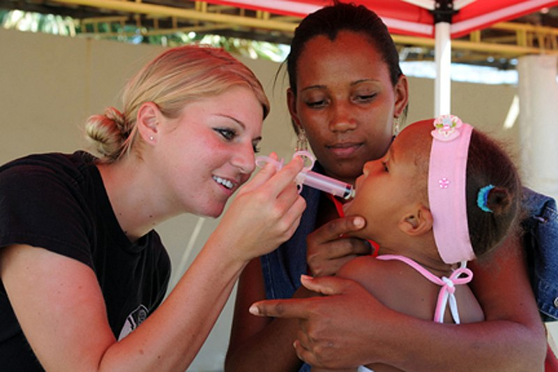 File:US Navy 081010-N-7955L-085 Air Force Senior Airman Alex Olson administers de-worming medication to a young patient.jpg