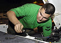 US Navy 081011-N-4954I-001 Aviation Support Equipment Technician 3rd Class Ben Rapp uses a wrench to adjust the engine throttle on a tow tractor.jpg